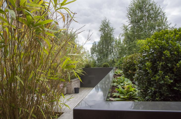 A long 'L' shaped planter forms a wall to edge a terrace.  Planters of this length are supplied in sections and assembled on site.