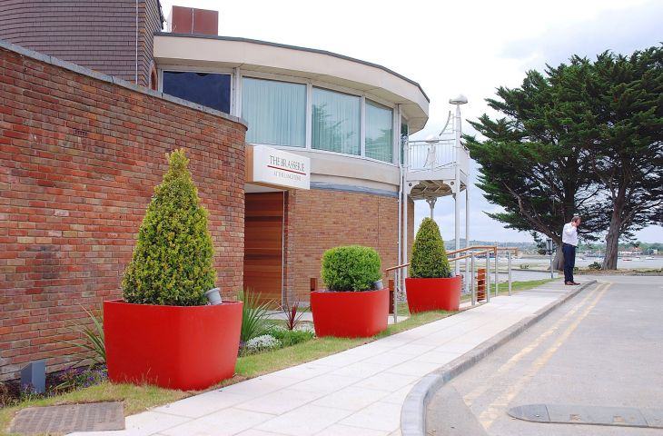 In bold Coral Red colour, the planters create a strong visual line along walkways.