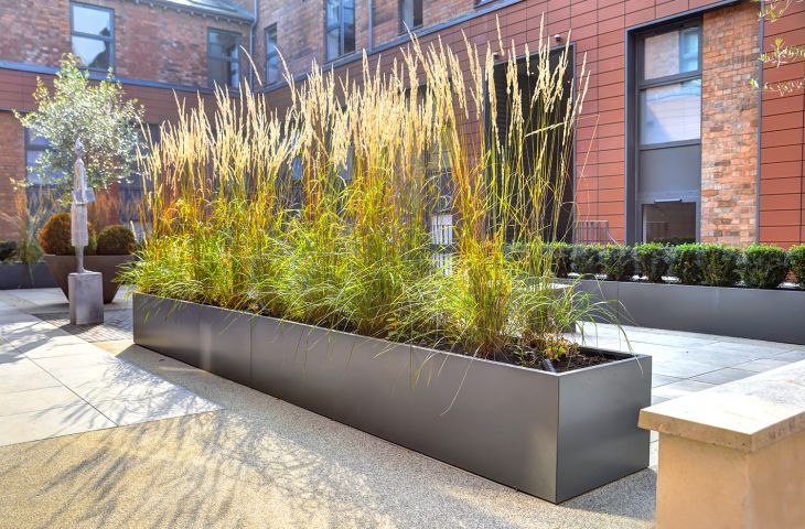 Powder coated steel planters in the courtyard of a residential development