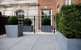 Collection of trough planters and low taper planters on private apartment balcony