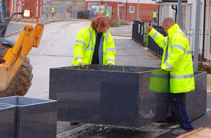 IOTA personnel installing 1300mm custom granite tree planter at Linden Homes, Basingstoke