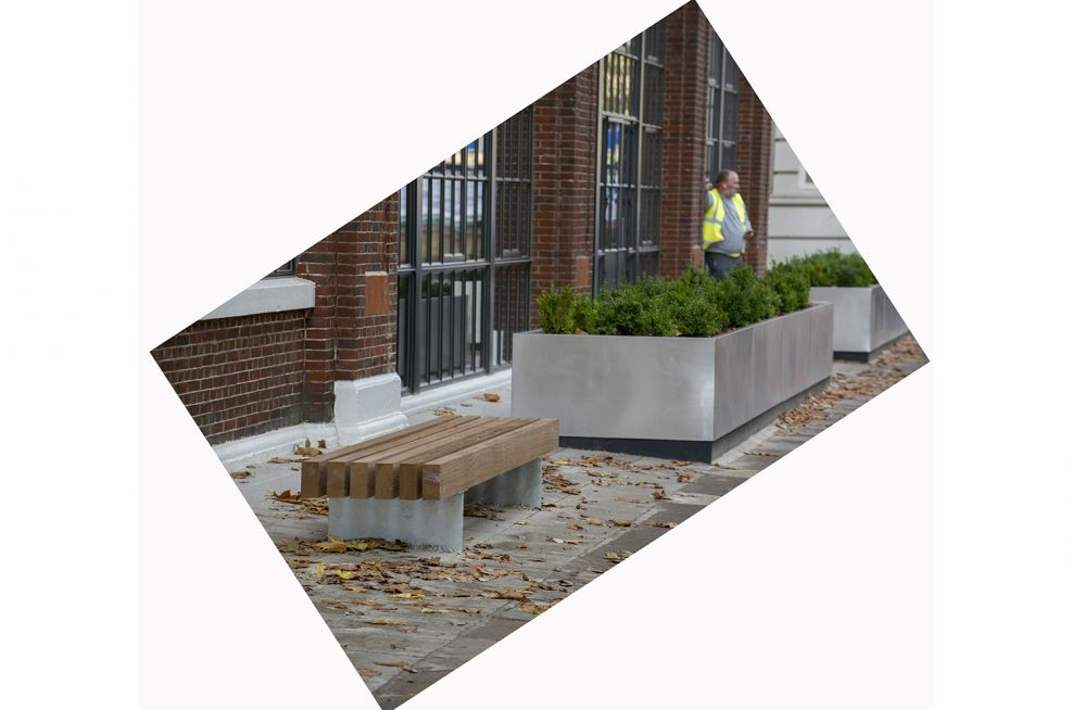 Brushed finish stainless steel planters alongside bench seating