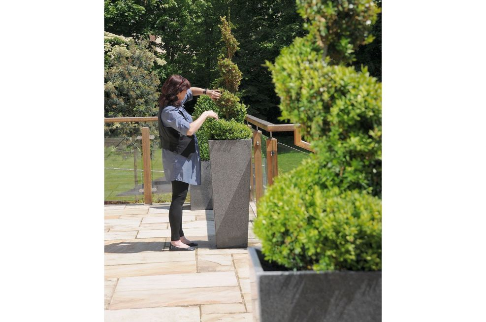 Lady Pruning A Tree In A Granite Tall Taper XXL Planter
